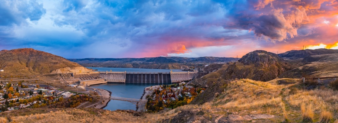 A powerful storm passes over Grand Coulee Dam at sunset.